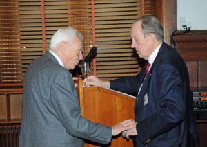 Foto Hasse Ferrold: Kassserer Peter Schønsted hilser på Carsten Dencker Nielsen, der bør medlemmerne velkommen til 2016. Se referat fra nytårskuren her